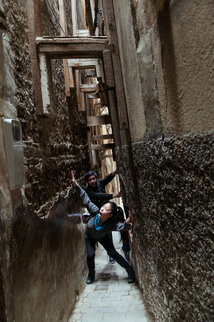 Narrow, dark alley in Fez between walls