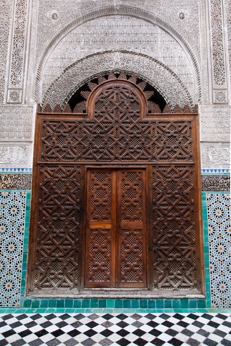 Tile work and carved door at Medersa el-Attarine in Fez